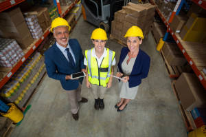 Warehouse manager standing with client and female worker